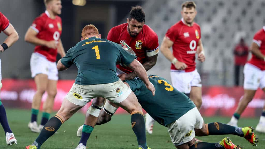 Courtney Lawes is tackled by Frans Malherbe and Steven Kitshoff